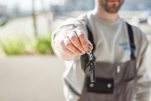 Une personne tends ses clefs de voiture vers la caméra.