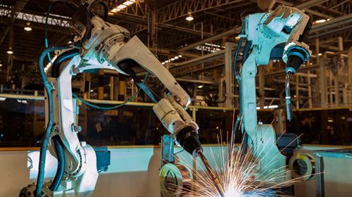 Deux bras robotiques à l'oeuvre dans une usine